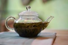 Μια καυτή εικόνα φωτογραφίας ποτών ενός δοχείου τσαγιού γυαλιού γέμισε με το φρέσκο πράσινο τσάι με ένα ανοικτό πράσινο υπόβαθρο Στοκ φωτογραφία με δικαίωμα ελεύθερης χρήσης