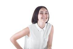Μια καλή και εύθυμη γυναίκα είναι γέλιο, που απομονώνεται σε ένα άσπρο υπόβαθρο Ένα βέβαιο θηλυκό brunette σε μια περιστασιακή μπ Στοκ Εικόνες