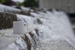 Μια κενή άσπρη κούπα καφέ στη μακριά πηγή νερού στοκ εικόνες με δικαίωμα ελεύθερης χρήσης