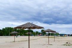 Μια κενή εγκαταλειμμένη παραλία στο άσχημο καιρό, κρύο φθινόπωρο στον εκτός εποχής με οι ομπρέλες θαλάσσης ενάντια στο μπλε ουραν στοκ φωτογραφίες