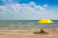 Μια κενή ηλιόλουστη αμμώδης παραλία θάλασσας με μια κίτρινη ομπρέλα και ένα θηλυκό τοποθετούν σε σάκκο Στοκ εικόνα με δικαίωμα ελεύθερης χρήσης