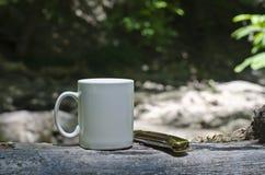Μια κενή κούπα καφέ και ένα διπλωμένο buck μαχαίρι Στοκ φωτογραφία με δικαίωμα ελεύθερης χρήσης