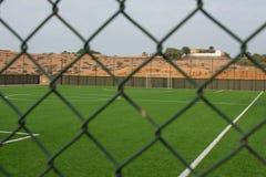 Μια κενή πίσσα ποδοσφαίρου είδε από έξω από το φράκτη στοκ φωτογραφία