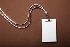 Μια κενή ταυτότητα, η ετικέττα ονόματος ενός υπαλλήλου ή ο επισκέπτης με έναν τρύγο δένουν σε ένα καφετί υπόβαθρο στοκ εικόνες