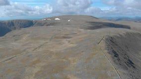 Μια κεραία αποκαλύπτει προς τα πίσω το μήκος σε πόδηα ενός σκωτσέζικου οροπέδιου συνόδου κορυφής με τον τεράστιο απότομο βράχο στ απόθεμα βίντεο