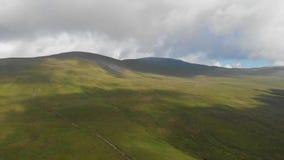 Μια κεραία αποκαλύπτει το μπροστινό μήκος σε πόδηα μιας μεγαλοπρεπούς χλοώδους κλίσης κορυφών βουνών με μια πορεία ιχνών, έναν μπ φιλμ μικρού μήκους
