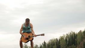 Μια κιθάρα παιχνιδιού ατόμων που στέκεται πάνω από το βουνό απόθεμα βίντεο