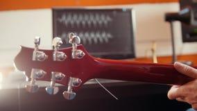 Μια κιθάρα παιχνιδιού προσώπων και καταγραφή του ήχου στο στούντιο Το κύμα μουσικής στην οθόνη απόθεμα βίντεο