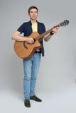 Μια κιθάρα παιχνιδιού νεαρών άνδρων στοκ φωτογραφία