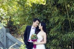 Μια κινεζική γαμήλια φωτογραφία ζευγών ` s που στέκονται σε μια αρχαία γέφυρα πετρών στο πάρκο του BO shui στη Σαγκάη Στοκ Εικόνα