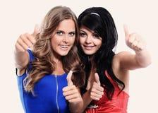 Μια κινηματογράφηση σε πρώτο πλάνο δύο νέων κοριτσιών που παρουσιάζουν αντίχειρές τους ενάντια Στοκ φωτογραφία με δικαίωμα ελεύθερης χρήσης