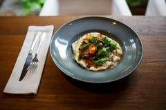 Μια κινηματογράφηση σε πρώτο πλάνο ενός νόστιμου πιάτου σε ένα μπλε πιάτο δίπλα σε ένα γεύμα έθεσε σε ένα σκοτεινό ξύλινο επιτραπ Στοκ Εικόνα
