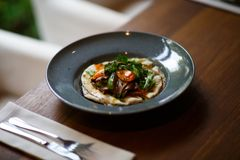 Μια κινηματογράφηση σε πρώτο πλάνο ενός νόστιμου πιάτου σε ένα μπλε πιάτο δίπλα σε ένα γεύμα έθεσε σε ένα σκοτεινό ξύλινο επιτραπ Στοκ Φωτογραφία