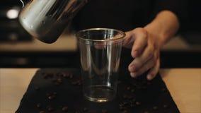 Μια κινηματογράφηση σε πρώτο πλάνο ενός χεριού barista που βάζει τους κύβους πάγου σε ένα πλαστικό φλυτζάνι φιλμ μικρού μήκους