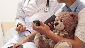 Μια κινηματογράφηση σε πρώτο πλάνο επιδεικνύει πώς ένας γιατρός μετρά την πίεση ενός μικρού κοριτσιού απόθεμα βίντεο