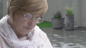 Μια κινηματογράφηση σε πρώτο πλάνο καροτσιού μιας ανάγνωσης γυναικών Φορά τα γυαλιά και ένα μαντίλι Κάθεται στο πεζούλι φιλμ μικρού μήκους