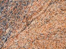 Μια κινηματογράφηση σε πρώτο πλάνο μιας σύστασης μιας γυαλισμένης κόκκινης επιφάνειας βράχου γρανίτη Στοκ Φωτογραφίες