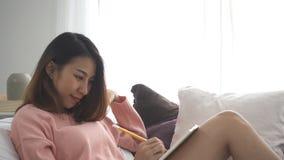 Μια κινηματογράφηση σε πρώτο πλάνο της νέας ευτυχούς συνεδρίασης κοριτσιών άνοιξε το βιβλίο στον καναπέ στο σπίτι Περιστασιακός τ απόθεμα βίντεο