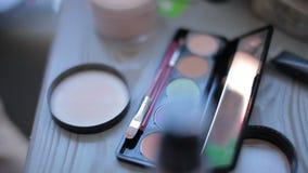Μια κινηματογράφηση σε πρώτο πλάνο, makeup πίνακας με τον εξοπλισμό makeup, φιλμ μικρού μήκους