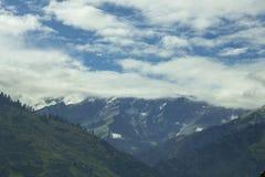 Μια κοιλάδα λόφων με τα βουνά χιονιού στοκ φωτογραφίες