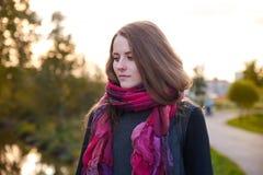 Μια κοκκινομάλλης νέα γυναίκα που περπατά γύρω από το πάρκο που ντύνεται σε έναν ομο στοκ εικόνες