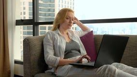 Μια κομψή γυναίκα βρίσκεται σε έναν καναπέ από το πανοραμικό παράθυρο που αγνοεί τους ουρανοξύστες και που χρησιμοποιεί το lap-to στοκ εικόνα με δικαίωμα ελεύθερης χρήσης
