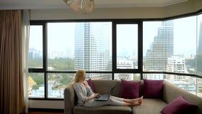 Μια κομψή γυναίκα βρίσκεται σε έναν καναπέ από το πανοραμικό παράθυρο που αγνοεί τους ουρανοξύστες και που χρησιμοποιεί το lap-to στοκ εικόνα