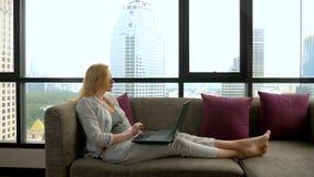 Μια κομψή γυναίκα βρίσκεται σε έναν καναπέ από το πανοραμικό παράθυρο που αγνοεί τους ουρανοξύστες και που χρησιμοποιεί το lap-to στοκ φωτογραφία με δικαίωμα ελεύθερης χρήσης