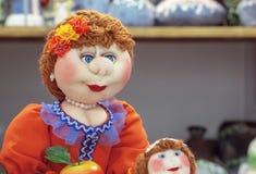 Μια κούκλα υφάσματος με τα μπλε μάτια σε ένα πορτοκαλί φόρεμα στοκ φωτογραφίες