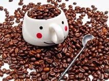 Μια κούπα καφέ με τα σιτάρια του ψημένου καφέ και ενός κουταλιού δίπλα στο ι Στοκ εικόνα με δικαίωμα ελεύθερης χρήσης
