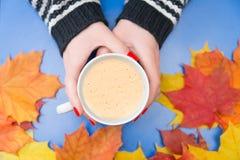 Μια κούπα καφέ στα χέρια μιας γυναίκας με τα φύλλα Στοκ φωτογραφία με δικαίωμα ελεύθερης χρήσης