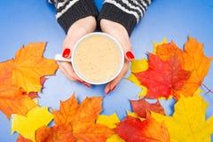Μια κούπα καφέ στα χέρια μιας γυναίκας με τα φύλλα Στοκ φωτογραφίες με δικαίωμα ελεύθερης χρήσης