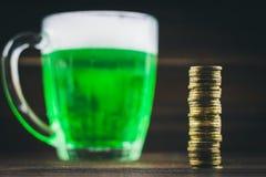 Μια κούπα της πράσινης μπύρας στον πίνακα φύλλα τριφυλλιού Στήθος του χρυσού, σωρός νομισμάτων Ημέρα StPatrick «s στοκ εικόνες με δικαίωμα ελεύθερης χρήσης