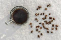 Μια κούπα του μαύρου καφέ στέκεται στο χιόνι, διεσπαρμένα φασόλια στοκ φωτογραφίες