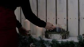 Μια κυρία ανάβει τα κεριά Η ζεστασιά και η ατμόσφαιρα των διακοπών Χριστουγέννων ψαλιδίζοντας τα ελάφια διακοσμήσεων που απομονών φιλμ μικρού μήκους