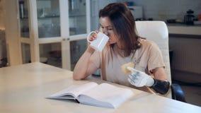 Μια κυρία με ένα προσθετικό χέρι πίνει το τσάι και διαβάζει ένα βιβλίο απόθεμα βίντεο