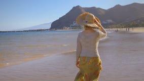 Μια κυρία σε ένα καπέλο περπατά κατά μήκος μιας τροπικής παραλίας στο ηλιοβασίλεμα φιλμ μικρού μήκους