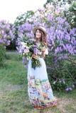 Μια κυρία σε ένα κομψό μακρύ φόρεμα, σε ένα καπέλο αχύρου και ένα τακτοποιημένο hairdo στέκεται σε έναν θερινό κήπο Ένα νέο κορίτ στοκ εικόνες