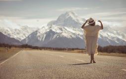 Μια κυρία χίπηδων boho στο άσπρο φόρεμα με το καπέλο στέκεται στο δρόμο με το AO στοκ εικόνες