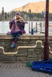 Μια κυρία busker παίζει το βιολί στο μέτωπο λιμνών στο πάρκο Earnslaw σε Queenstown στοκ φωτογραφία