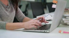 Μια κυρία Sitting στη δακτυλογράφηση γραφείων σε ένα lap-top απόθεμα βίντεο