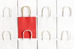 Μια κόκκινη τσάντα αγορών στο υπόβαθρο των άσπρων τσαντών που απομονώνεται στο άσπρο υπόβαθρο Στοκ εικόνες με δικαίωμα ελεύθερης χρήσης