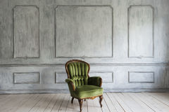 Μια κλασική πολυθρόνα ενάντια σε έναν άσπρους τοίχο και ένα πάτωμα διάστημα αντιγράφων Στοκ Εικόνες