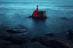 Μια λυπημένη γυναίκα κοντά στη θάλασσα το βράδυ στοκ εικόνα με δικαίωμα ελεύθερης χρήσης