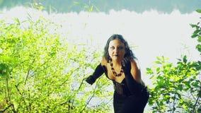 Μια μάγισσα στα μαύρα ενδύματα στην ακτή της λίμνηση αποκριές Ύφος Gothick απόθεμα βίντεο