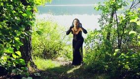 Μια μάγισσα στα μαύρα ενδύματα στη λίμνη με τις συγκινήσεις του θυμού στο πρόσωπό της αποκριές Ύφος Gothick φιλμ μικρού μήκους