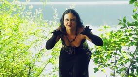 Μια μάγισσα στα μαύρα ενδύματα στη λίμνη με τις συγκινήσεις του θυμού στο πρόσωπό της αποκριές Ύφος Gothick απόθεμα βίντεο