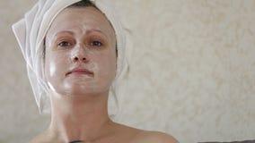 Μια μέσης ηλικίας γυναίκα εφαρμόζει μια ενυδατική μάσκα στο πρόσωπο απόθεμα βίντεο