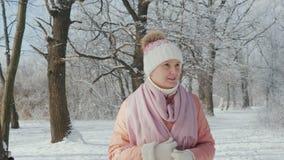 Μια μέσης ηλικίας γυναίκα περπατά σε ένα χειμερινό πάρκο μια σαφή ημέρα, χιονίζει απόθεμα βίντεο