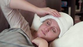 Μια μέσης ηλικίας γυναίκα που βρίσκεται στον καναπέ Έχει ένα κρύο, ένας πονοκέφαλος απόθεμα βίντεο